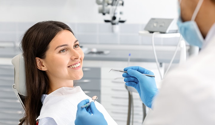 a woman smiling in front of her dentist for a dental checkup